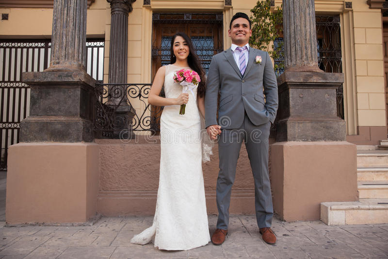 Happy couple in a courthouse. Full length portrait of a cute bridal couple holding hands outside a courthouse royalty free stock photos