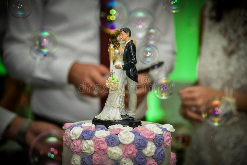 A happy couple cutting the wedding cake. On a wedding day, in front of their family and friends, while water baloons are falling around them royalty free stock images