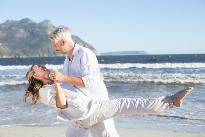 Happy couple dancing on the beach together stock image