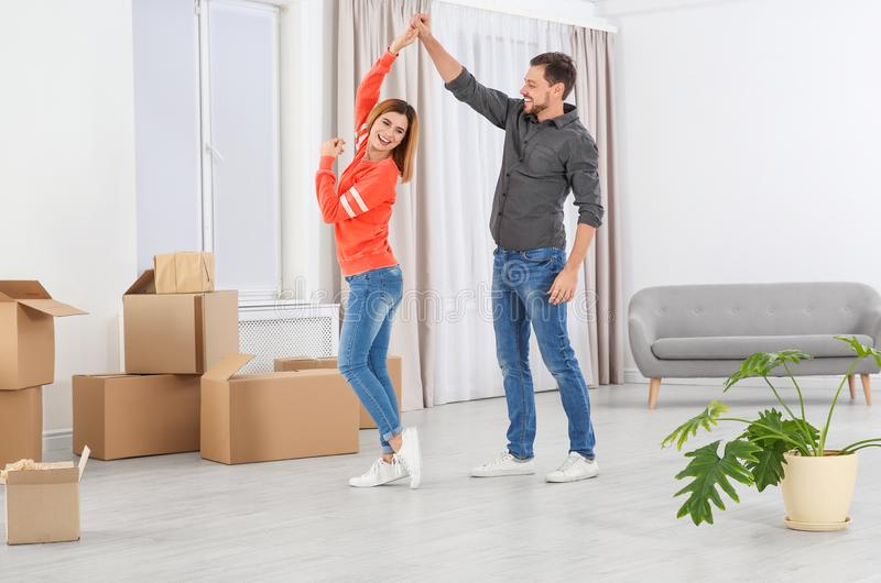 Happy couple dancing near moving boxes in new house stock photography