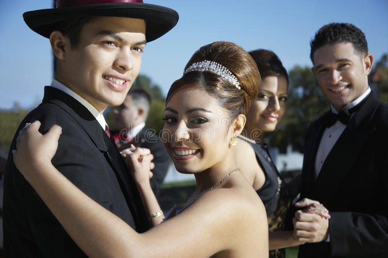 Happy couple dancing at Quinceanera. Happy couple dancing together with friends in the background at Quinceanera royalty free stock image