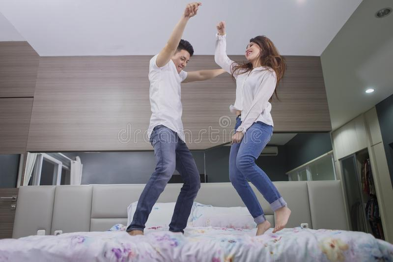 Happy couple dancing together on the bed royalty free stock images