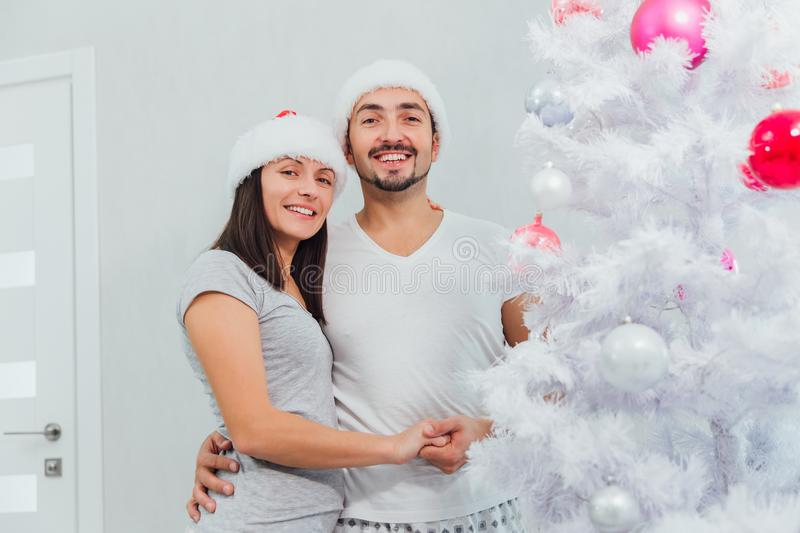 Happy Couple Decorating Christmas Tree in their Home. Smiling Man and Woman together Celebrating Christmas or New Year stock photo