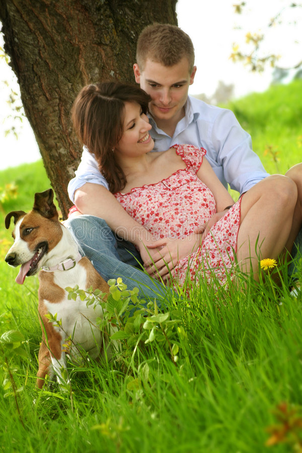 Happy couple with a dog. A happy couple is sitting on a green meadow with a dog