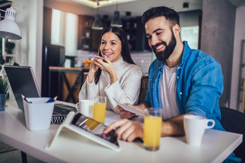 Couple doing business together working at home on the laptop. Happy couple doing business together working at home on the laptop stock photos