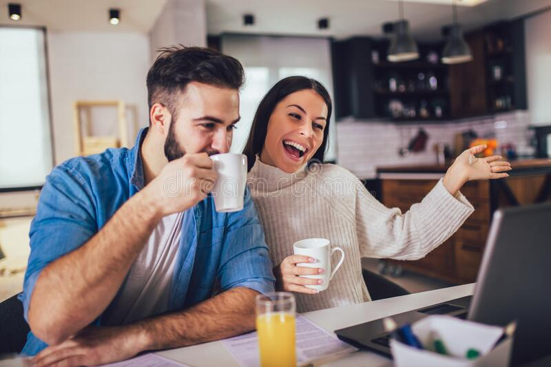 Couple doing business together working at home on the laptop. Happy couple doing business together working at home on the laptop royalty free stock photography