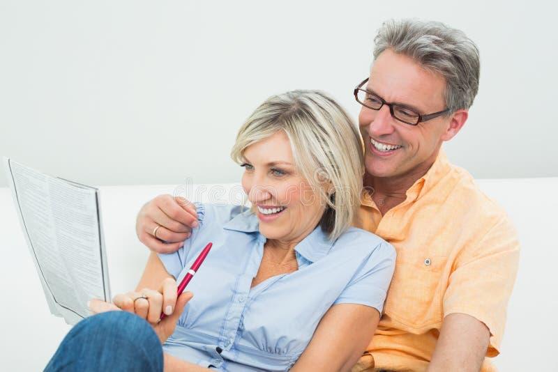 Happy couple doing the newspaper crossword puzzle at home. Happy men and women doing the newspaper crossword puzzle in the living room at home stock image