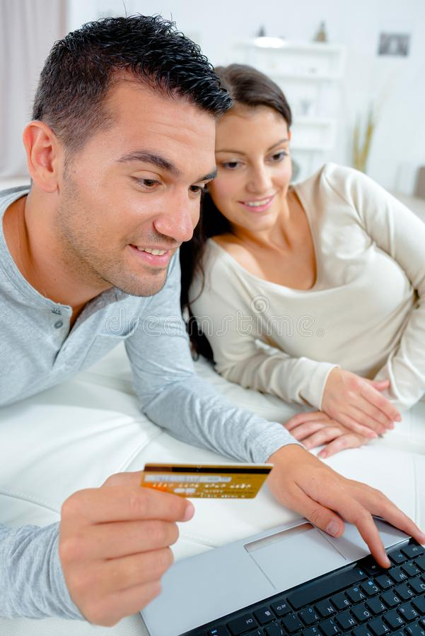 Happy couple doing online shopping with credit card and laptop royalty free stock photography