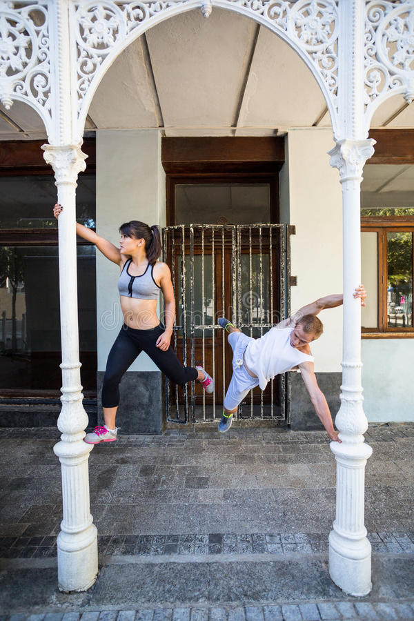 Happy couple doing parkour in the city royalty free stock photo
