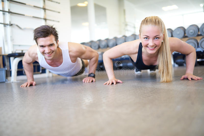 Happy Couple Doing Push Ups Together in Gym. Low Angle View of Couple Doing Push Ups Together or Planking in Gym, Front View of Happy Healthy Couple Working Out royalty free stock photography