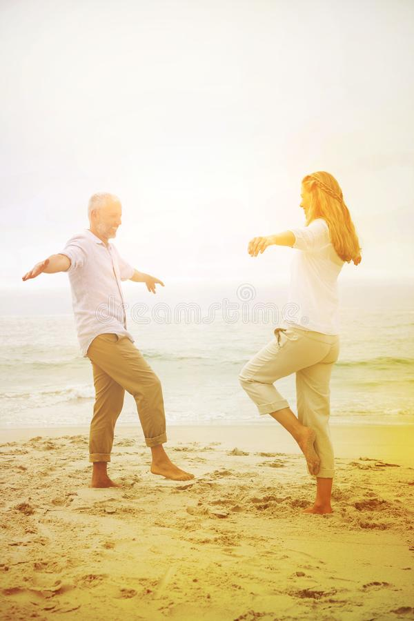Happy couple doing yoga pose stock image