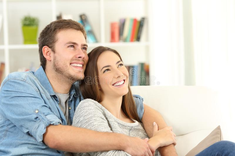 Happy couple dreaming looking above at home stock photos