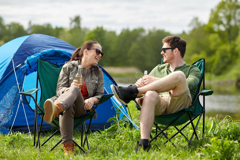Happy couple drinking beer at campsite tent. Camping, travel, tourism, hike and people concept - happy couple drinking beer or cider at campsite tent stock image