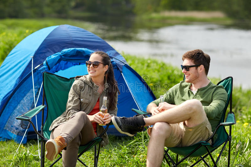 Happy couple drinking beer at campsite tent. Camping, travel, tourism, hike and people concept - happy couple drinking beer or cider at campsite tent stock images