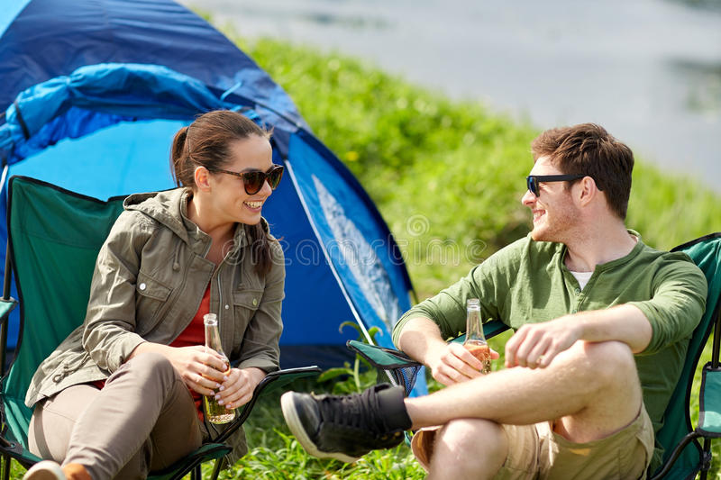 Happy couple drinking beer at campsite tent. Camping, travel, tourism, hike and people concept - happy couple drinking beer or cider at campsite tent stock photos