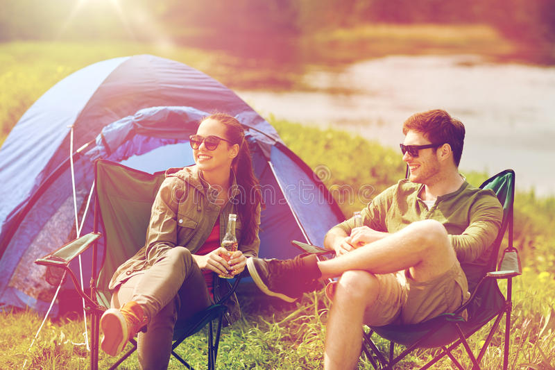 Happy couple drinking beer at campsite tent. Camping, travel, tourism, hike and people concept - happy couple drinking beer or cider at campsite tent royalty free stock photos