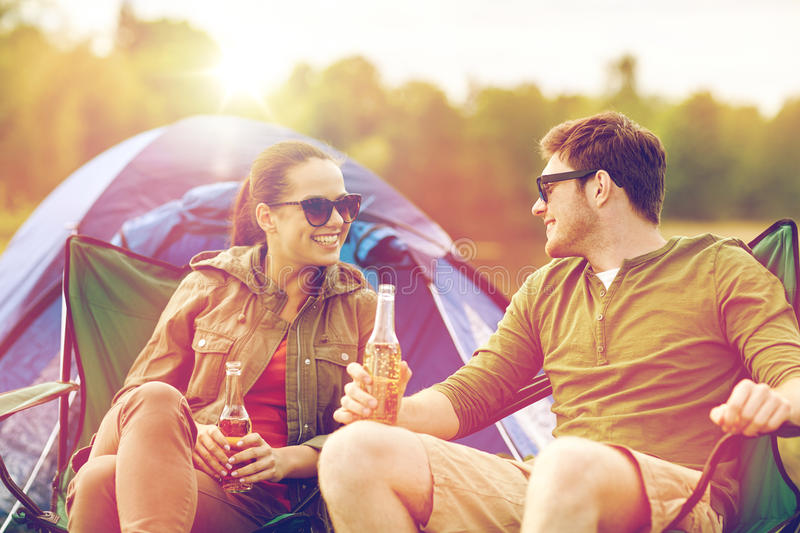 Happy couple drinking beer at campsite tent. Camping, travel, tourism, hike and people concept - happy couple drinking beer or cider at campsite tent royalty free stock photography