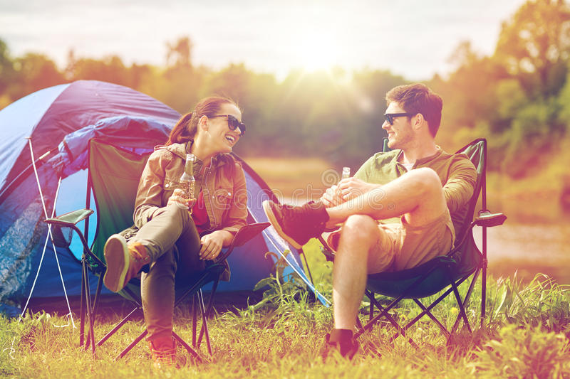 Happy couple drinking beer at campsite tent. Camping, travel, tourism, hike and people concept - happy couple drinking beer or cider at campsite tent stock photography