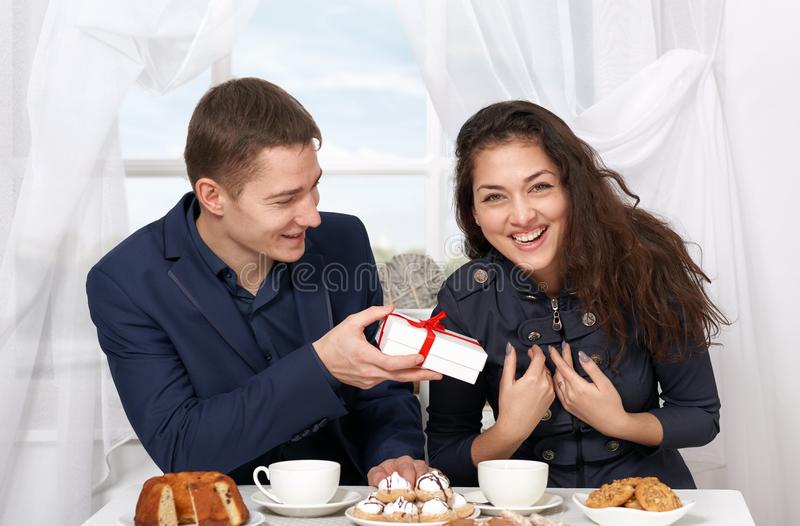 Happy couple drinking coffee and having fun, man give very funny gifts - love and holiday concept. Happy couple drinking coffee and having fun, men give very stock photos