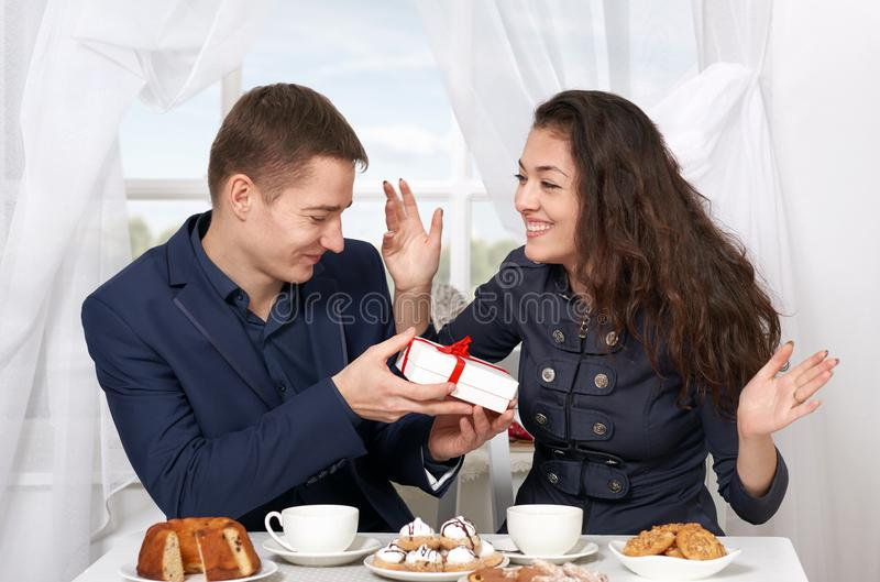 Happy couple drinking coffee and having fun, man give very funny gifts - love and holiday concept. Happy couple drinking coffee and having fun, men give very royalty free stock images