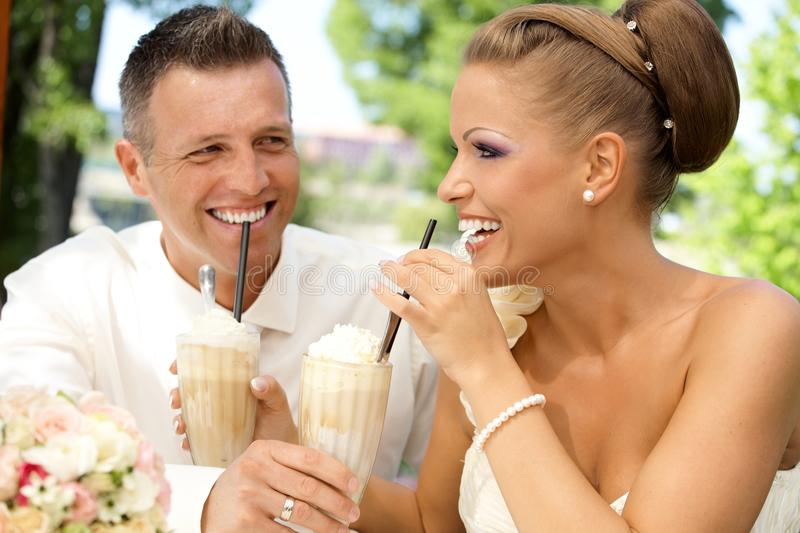 Happy couple drinking ice coffee on wedding-day. Happy young couple drinking ice coffee through straw on wedding-day outdoors. Laughing happy stock images