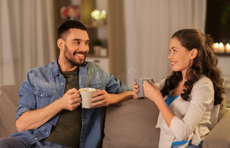 Happy couple drinking tea or coffee at home stock photos