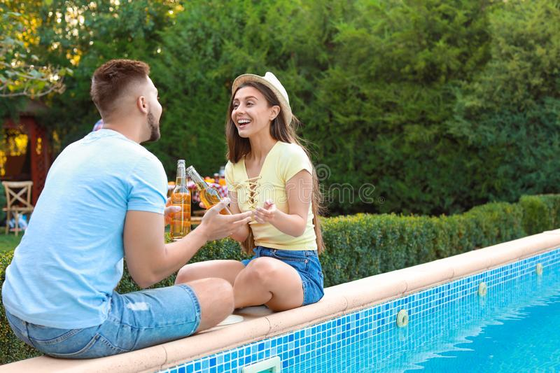 Happy couple with drinks at barbecue party near swimming pool royalty free stock image