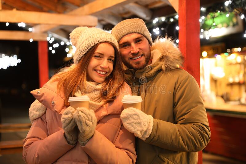 Couple with drinks at Christmas fair royalty free stock image