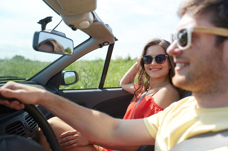 Happy couple driving in cabriolet car at country stock photo