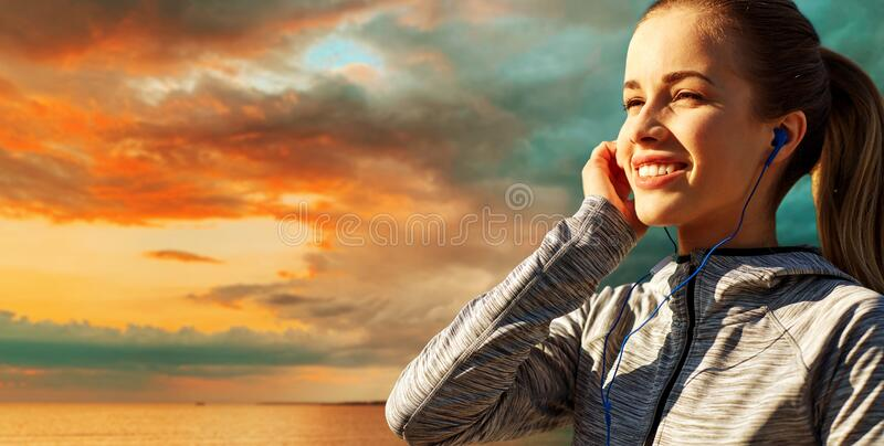 Happy couple with earphones running over sea royalty free stock photography
