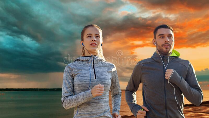 Happy couple with earphones running over sea royalty free stock images
