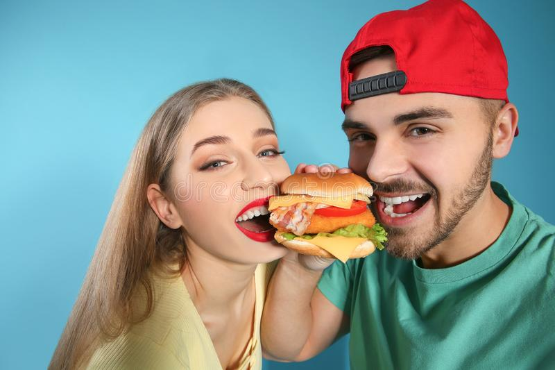 Happy couple eating burger royalty free stock photo