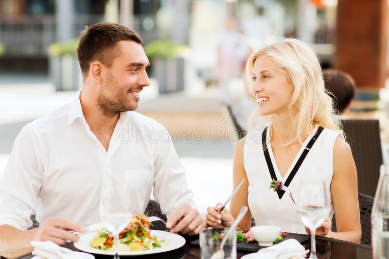 Happy couple eating dinner at restaurant terrace. Love, date, people, holidays and relations concept - happy couple eating salad for dinner at cafe or restaurant royalty free stock images