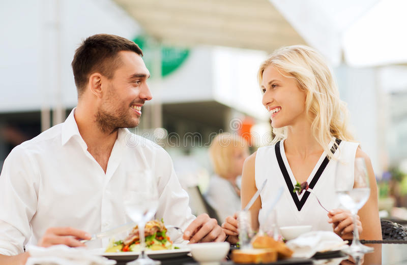 Happy couple eating dinner at restaurant terrace. Love, date, people, holidays and relations concept - happy couple eating salad for dinner at cafe or restaurant stock image