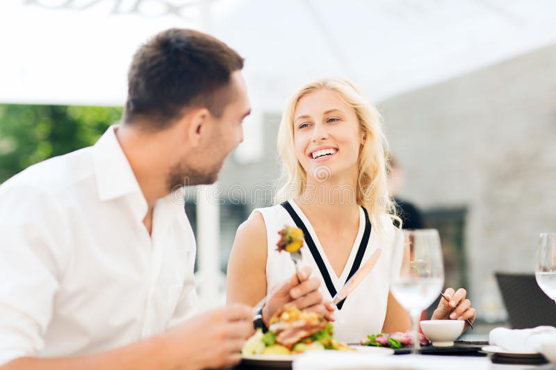 Happy couple eating dinner at restaurant terrace. Love, date, people, holidays and relations concept - happy couple eating salad for dinner at cafe or restaurant stock photo