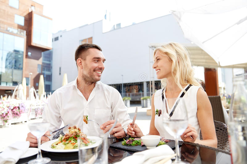 Happy couple eating dinner at restaurant terrace. Love, date, people, holidays and relations concept - happy couple eating salad for dinner at cafe or restaurant stock photography