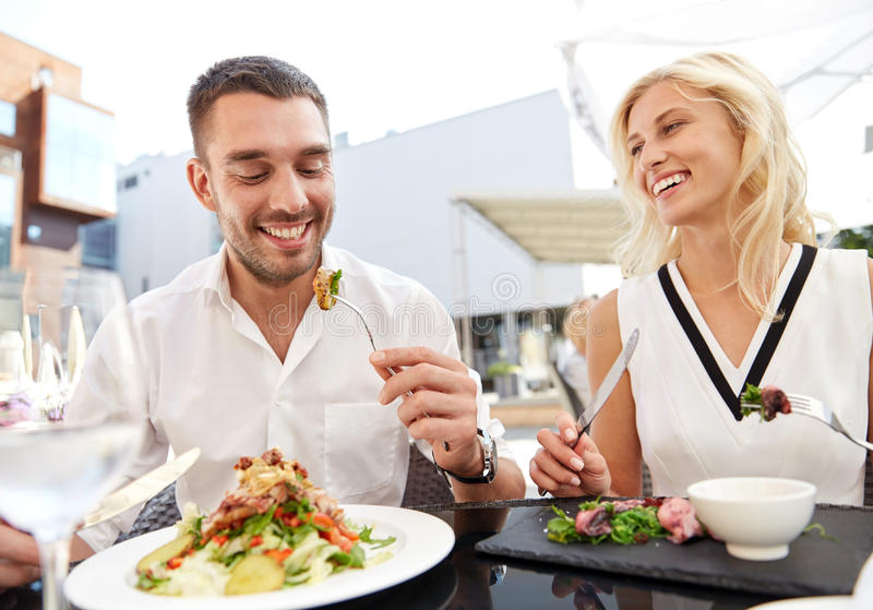 Happy couple eating dinner at restaurant terrace. Love, date, people, holidays and relations concept - happy couple eating salad for dinner at cafe or restaurant royalty free stock photos