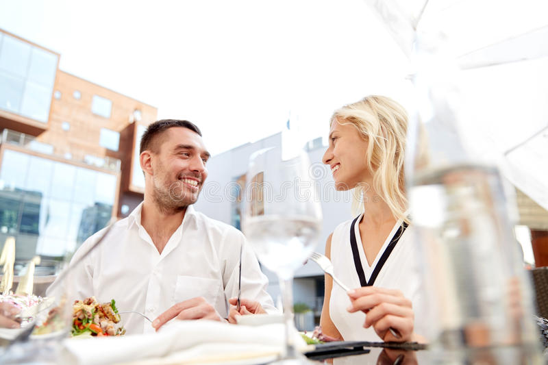 Happy couple eating dinner at restaurant terrace. Love, date, people, holidays and relations concept - happy couple eating salad for dinner at cafe or restaurant stock images