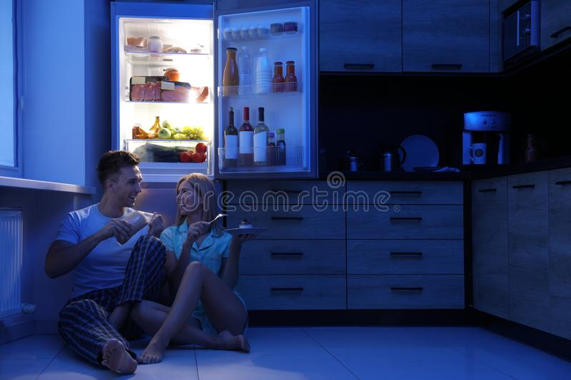Happy couple eating near refrigerator in kitchen stock photo
