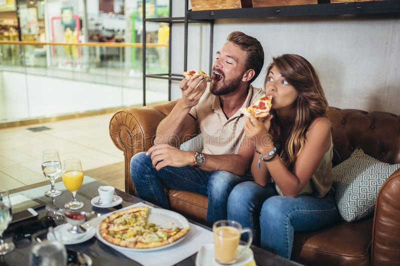 Happy couple eating pizza in a restaurant stock photos