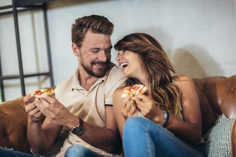 Happy couple eating pizza in a restaurant stock photography