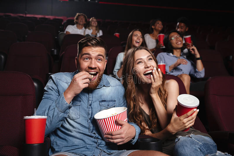 Happy couple eating popcorn and laughing. While sitting and watching movie at the cinema stock photography
