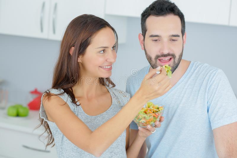 Happy couple eating vegetable salad stock photos