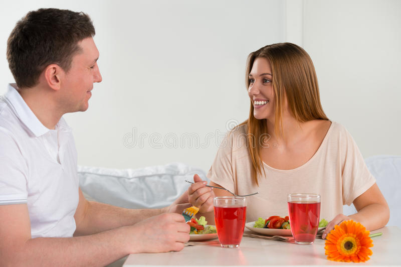 Happy couple eating vegetable salad stock photo