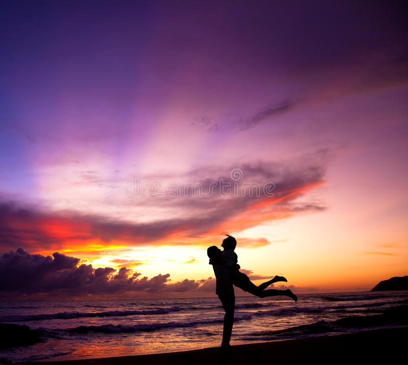 Happy couple embracing on the beach stock photo
