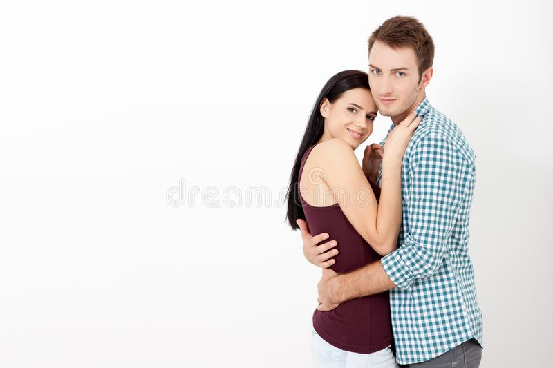 Happy couple embracing and looking camera on white background stock images