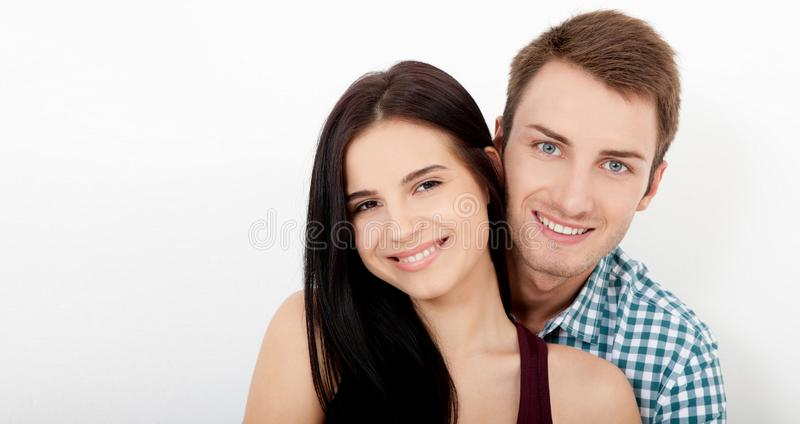 Happy couple embracing and looking camera on white background stock photos