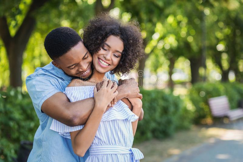 Happy couple embracing in park on sunny day royalty free stock photos