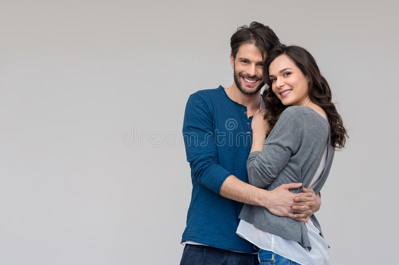 Happy couple embracing. Portrait of happy couple looking at camera against gray background stock image
