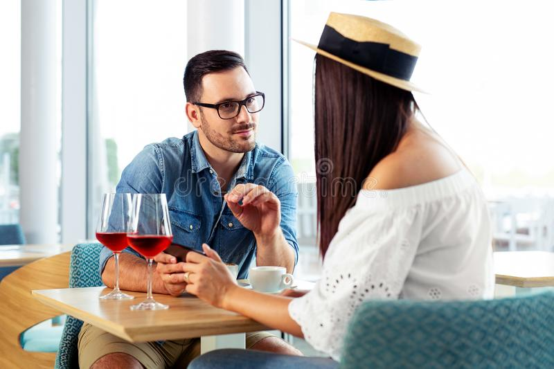 Happy couple enjoying in the afternoon with a cup of coffee and a glass of wine. Happy young couple enjoying in the afternoon with a cup of coffee and a glass of stock images